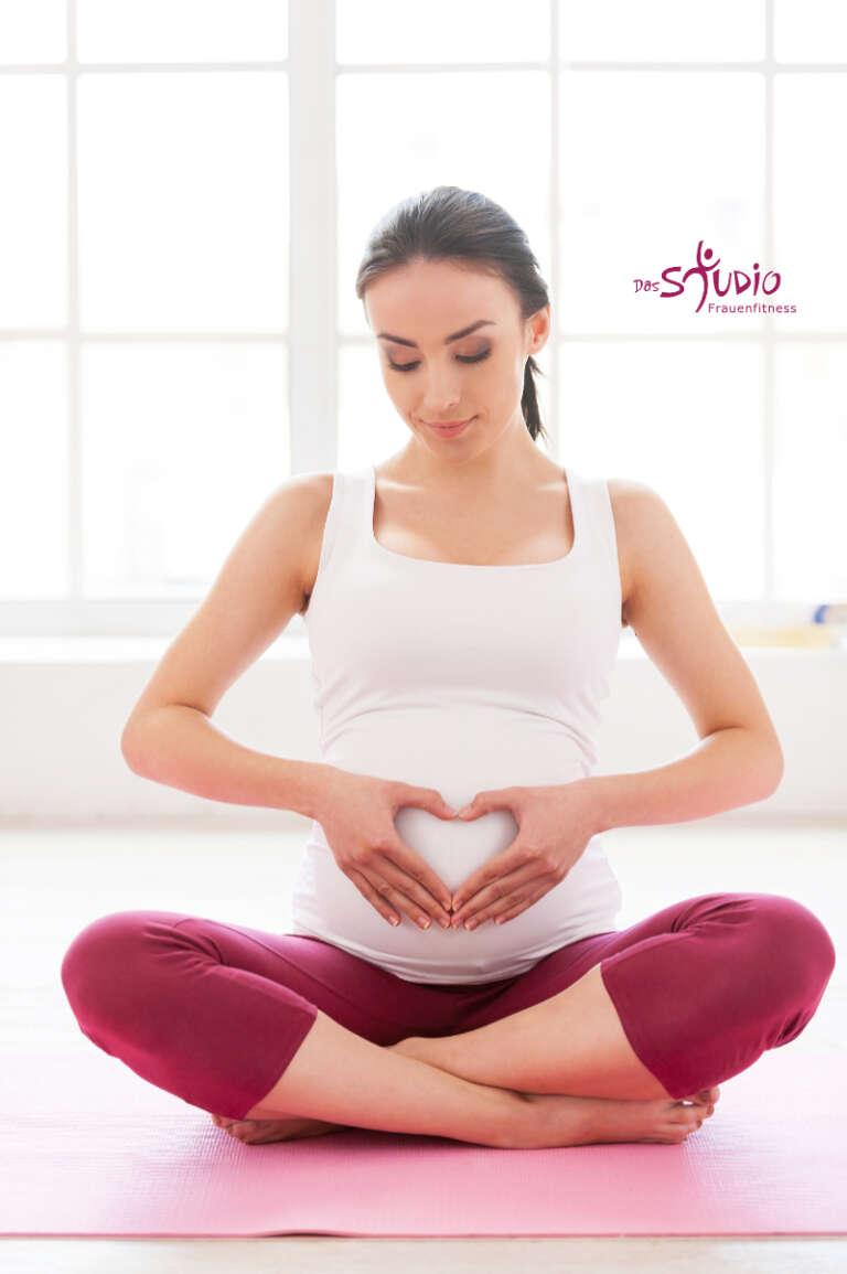 eine junge, schwangere Frau sitzt im Lotussitz auf ihrer YogamatteHänden vor ihren Bauch.