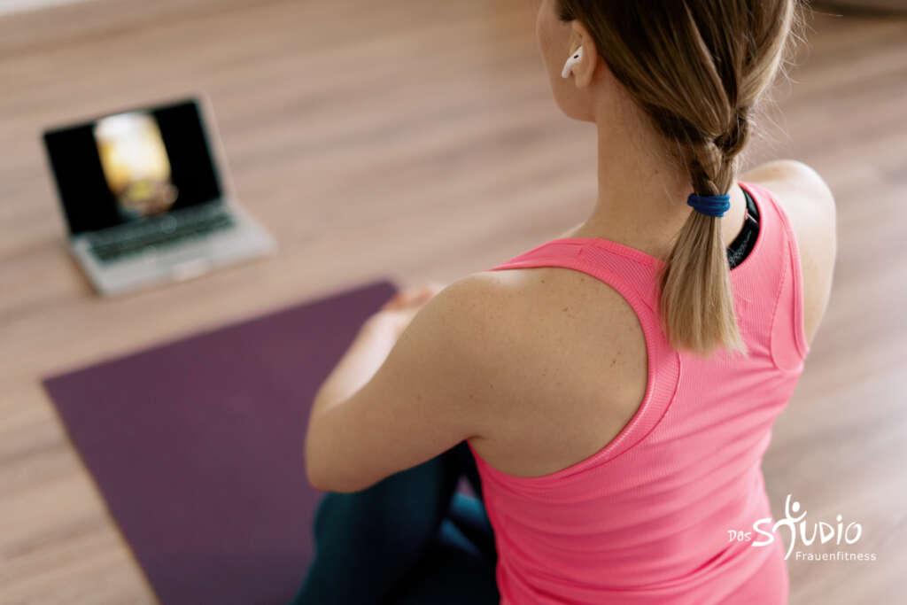 Attraktive Frau praktiziert Online-Yoga zu Hause