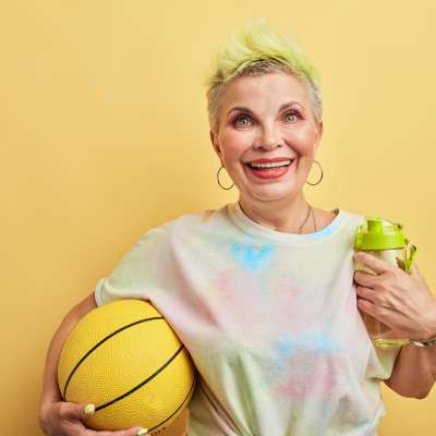 glamour kind of sport. gorgeous granny playing games with her grandsons, isolated yellow background, studio shot.